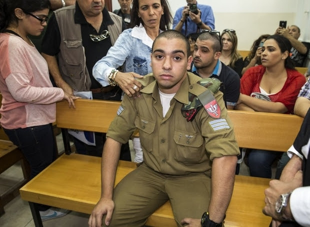 Israeli soldier Elor Azaria, who was caught on video shooting a wounded Palestinian assailant in the head as he lay on the ground, sits during a hearing at a military appeals court in Tel Aviv during which he was charged with manslaughter on April 18, 2016. Prosecutors presented the indictment to a military court over the March 24 killing, which occurred minutes after the Palestinian had stabbed another soldier and lay prone on the ground wounded by gunfire, according to Israeli authorities. He was also charged with conduct unbecoming of his rank and position in the army. / AFP PHOTO / JACK GUEZ