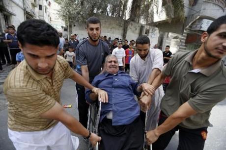 des-jeunes-palestiniens-aident-une-personne-agee-a-evacuer-son-habitation-apres-avoir-recu-une-alert