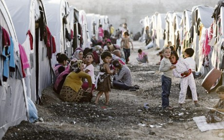 Kurdish refugees from the Syrian town of Kobani sit in front of their tents in a camp in the southeastern town of Suruc